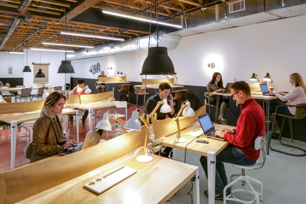 Coworkers working at personal and group desks at The Fort