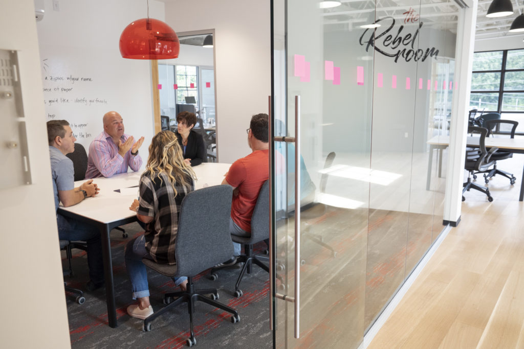 Coworkers holding a meeting in a conference room at Vibe Coworks